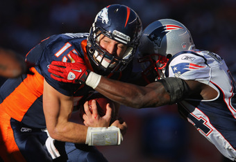 DENVER, CO - DECEMBER 18:  Quarterback Tim Tebow of the Denver Broncos is tackled by strong safety James Ihedigbo #44 of the New England Patriots at Sports Authority Field at Mile High on December 18, 2011 in Denver, Colorado.  (Photo by Doug Pensinger/Ge