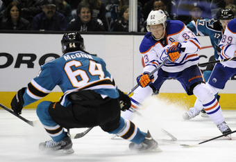SAN JOSE, CA - DECEMBER 17:  Ales Hemsky #83 of the Edmonton Oilers passes the puck by Jamie McGinn #64 of the San Jose Sharks at HP Pavilion at San Jose on December 17, 2011 in San Jose, California. The Sharks won the game 3-2. (Photo by Thearon W. Hende