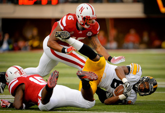 LINCOLN, NE - NOVEMBER 25: Wide receiver Don Shumpert #8 of the Iowa Hawkeyes is tripped up by cornerback Alfonzo Dennard #15 and linebacker Alonzo Whaley #45 of the Nebraska Cornhuskers during their game at Memorial Stadium November 25, 2011 in Lincoln,