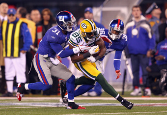 EAST RUTHERFORD, NJ - DECEMBER 04:  Greg Jennings #85 of the Green Bay Packers makes a reception against Aaron Ross #31 and Will Blackmon #36 of the New York Giants at MetLife Stadium on December 4, 2011 in East Rutherford, New Jersey.  (Photo by Al Bello
