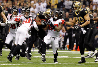NEW ORLEANS, LA - DECEMBER 26:  Running back Pierre Thomas #23 of the New Orleans Saints runs the ball between cornerback Brent Grimes #20 and defensive end Lawrence Sidbury #90 of the Atlanta Falcons in the first half at the Mercedes-Benz Superdome on De