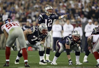 GLENDALE, AZ - FEBRUARY 03:  Quarterback Tom Brady #12 of the New England Patriots directs the offense at the line of scrimmage against the New York Giants during Super Bowl XLII on February 3, 2008 at the University of Phoenix Stadium in Glendale, Arizon