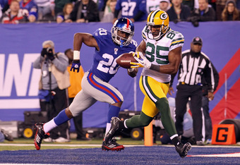 EAST RUTHERFORD, NJ - DECEMBER 04:  Greg Jennings #85 of the Green Bay Packers catches a 2-yard touchdown reception in the third quarter against Prince Amukamara #20 of the New York Giants at MetLife Stadium on December 4, 2011 in East Rutherford, New Jer