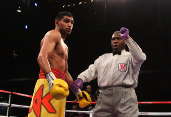 WASHINGTON, DC - DECEMBER 10:  Referee Joe Cooper deducts a point from Amir Khan for excessive shoving against Lamont Peterson during their WBA Super Lightweight and IBF Junior Welterweight title fight at Washington Convention Center on December 10, 2011