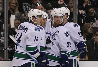 LOS ANGELES, CA - DECEMBER 31:  (L-R) Alexandre Burrows #14, Kevin Bieksa #3, Henrik Sedin #33 and Daniel Sedin #22 of the Vancouver Canucks celebrate Bieksa's first-period goal against the Los Angeles Kings in the first period during the NHL game at Stap
