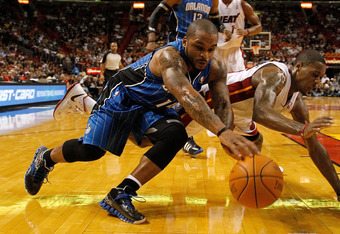 MIAMI, FL - DECEMBER 18:  Jameer Nelson #14 of the Orlando Magic fights for a loose ball with Mario Chalmers #15 of the Miami Heat during a preseason game at AmericanAirlines Arena on December 18, 2011 in Miami, Florida. NOTE TO USER: User expressly ackno