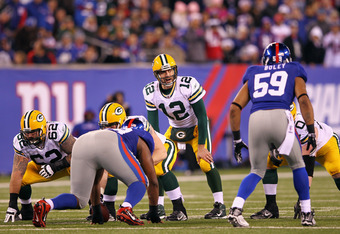 EAST RUTHERFORD, NJ - DECEMBER 04:  Aaron Rodgers #12 of the Green Bay Packers calls signals out at the line of scrimmage against Michael Boley #59 of the New York Giants at MetLife Stadium on December 4, 2011 in East Rutherford, New Jersey.  (Photo by Al