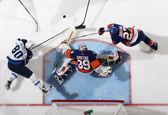 UNIONDALE, NY - NOVEMBER 03: Nik Antropov #80 of the Winnipeg Jets is tripped up as Rick DiPietro #39 of the New York Islanders makes the save at the Nassau Veterans Memorial Coliseum on November 3, 2011 in Uniondale, New York. The Jets defeated the Islan