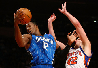NEW YORK - NOVEMBER 29:  Dwight Howard #12 of the Orlando Magicgrabs a rebound over David Lee #42 of the New York Knicks at Madison Square Garden November 29, 2009 in New York City. NOTE TO USER: User expressly acknowledges and agrees that, by downloading