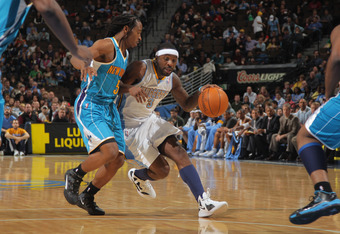 DENVER, CO - JANUARY 09:  Ty Lawson #3 of the Denver Nuggets drives the ball against Carldell Johnson #5 of the New Orleans Hornets at the Pepsi Center on January 9, 2012 in Denver, Colorado. The Hornets defeated the Nuggets 94-81. NOTE TO USER: User expr