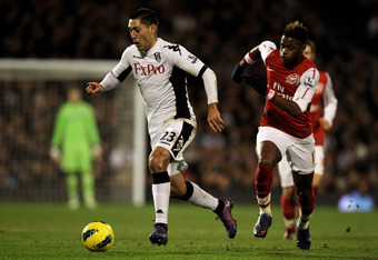 LONDON, ENGLAND - JANUARY 02:  Clint Dempsey of Fulham is pursued by Alex Song of Arsenal during the Barclays Premier League match between Fulham and Arsenal at Craven Cottage on January 2, 2012 in London, England.  (Photo by Clive Rose/Getty Images)