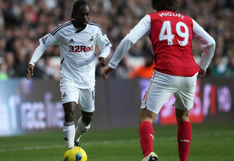 SWANSEA, WALES - JANUARY 15: Nathan Dyer of Swansea City takes on Ignasi Miquel of Arsenal during the Barclays Premier League match between Swansea City and Arsenal at Liberty Stadium on January 15, 2012 in Swansea, Wales.  (Photo by Michael Steele/Getty