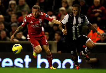 LIVERPOOL, ENGLAND - DECEMBER 30:  Danny Simpson of Newcastle United competes with Craig Bellamy of Liverpool during the Barclays Premier League match between Liverpool and Newcastle United at Anfield on December 30, 2011 in Liverpool, England.  (Photo by