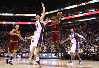 PHOENIX, AZ - JANUARY 12:  Kyrie Irving #2 of the Cleveland Cavaliers drives to the basket past Marcin Gortat #4 of the Phoenix Suns during the NBA game at US Airways Center on January 12, 2012 in Phoenix, Arizona.  NOTE TO USER: User expressly acknowledg