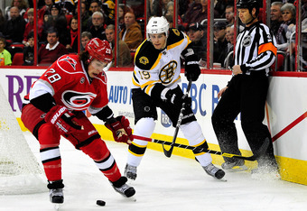 RALEIGH, NC - JANUARY 14:  Justin Faulk #28 of the Carolina Hurricanes protects the puck from Tyler Seguin #19 of the Boston Bruins during play at the RBC Center on January 14, 2012 in Raleigh, North Carolina.  (Photo by Grant Halverson/Getty Images)