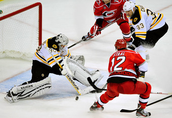 RALEIGH, NC - JANUARY 14:  Goalkeeper Tim Thomas #30 of the Boston Bruins stops a shot by Eric Staal #12 of the Carolina Hurricanes during play at the RBC Center on January 14, 2012 in Raleigh, North Carolina. The Hurricanes won 4-2.  (Photo by Grant Halv