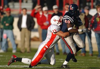 SHREVEPORT, LA - DECEMBER 27:  Linebacker Ira Cooper #11 of the University of Nebraska Huskers tackles tight end Eric Rice #80 of Mississippi Ole Miss Rebels during during the MainStay Independence Bowl at Independence Stadium on December 27, 2002 in Shre