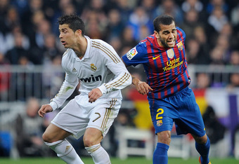MADRID, SPAIN - JANUARY 18:  Cristiano Ronaldo (L) of Real Madrid is challenged by Daniel Alves of Barcelona during the Copa del Rey Quarter Finals match between Real Madrid and Barcelona at Estadio Santiago Bernabeu on January 18, 2012 in Madrid, Spain.