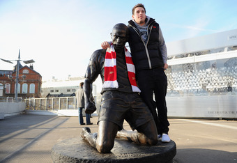 LONDON, ENGLAND - DECEMBER 10:  A fan poses with the Thierry Henry statue is seen outside the stadium ahead of the Barclays Premier League match between Arsenal and Everton at Emirates Stadium on December 10, 2011 in London, England.  (Photo by Michael Re