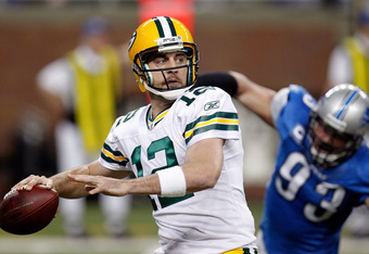 DETROIT, MI - NOVEMBER 24:  Quarterback Aaron Rodgers #12 of the Green Bay Packers looks to pass as defensive end Kyle Vanden Bosch #93 of the Detroit Lions rushes in during the first quarter of the Thanksgiving Day game at Ford Field on November 24, 2011