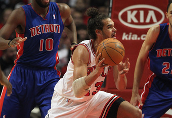 CHICAGO, IL - JANUARY 09: Joakim Noah #13 of the Chicago Bulls passes under pressure from Greg Monroe #10 of the Detroit Pistons at the United Center on January 9, 2012 in Chicago, Illinois. The Bulls defeated the Pistons 92-68. NOTE TO USER: User express