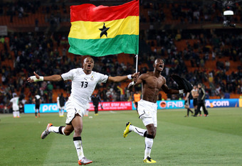 JOHANNESBURG, SOUTH AFRICA - JUNE 23:  Andre Ayew (L) and John Pantsil of Ghana celebrate with a national flag having qualified for the next round, despite losing the match, during the 2010 FIFA World Cup South Africa Group D match between Ghana and Germa