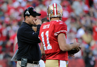 SAN FRANCISCO, CA - JANUARY 14:  Head coach Jim Harbaugh of the San Francisco 49ers talks with quarterback Alex Smith #11 in the third quarter against the New Orleans Saints during the NFC Divisional playoff game at Candlestick Park on January 14, 2012 in