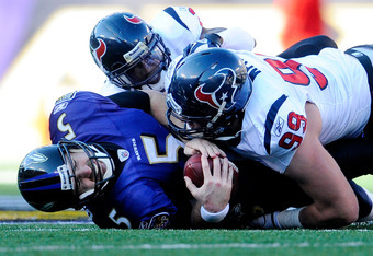 BALTIMORE, MD - JANUARY 15:  Quarterback Joe Flacco #5 of the Baltimore Ravens is sacked by  J.J. Watt #99 and  Brice McCain #21 of the Houston Texans during the second quarter of the AFC Divisional playoff game at M&T Bank Stadium on January 15, 2012 in