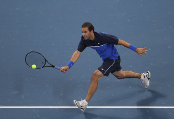 BEIJING, CHINA - SEPTEMBER 30:  Pete Sampras of the United States completes Marat Safin of Russia during an exhibition match to inaugurate the opening of the new stadium during the China Open on September 30, 2011 in Beijing, China.  (Photo by Feng Li/Get