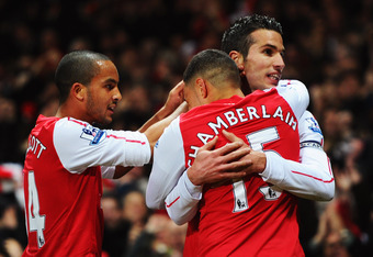 LONDON, ENGLAND - JANUARY 22:  Robin van Persie of Arsenal (R) celebrates with Theo Walcott (L)and Alex Oxlade-Chamberlain (C) as he scores their first goal during the Barclays Premier League match between Arsenal and Manchester United at Emirates Stadium