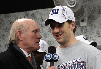 SAN FRANCISCO, CA - JANUARY 22:  Eli Manning #10 of the New York Giants is interviewed in the locker room by Terry Bradshaw as he celebrates in the locker room with the George Halas Trophy NFC Championship trophy after the Giants won 20-17 in overtime aga