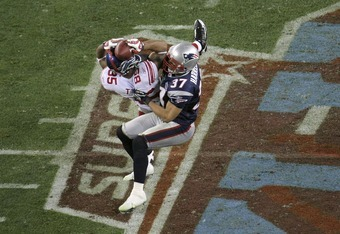 GLENDALE, AZ - FEBRUARY 03:  David Tyree #85 of the New York Giants catches a 32-yard pass from Eli Manning #10 as Rodney Harrison #37 of the New England Patriots attempts to knock it out in the fourth quarter of Super Bowl XLII on February 3, 2008 at the