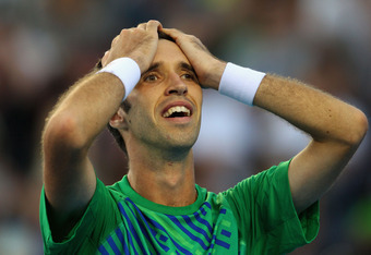 MELBOURNE, AUSTRALIA - JANUARY 21:  Mikhail Kukushkin of Kazakhstan celebrates winning his third round match against Gael Monfils of France during day six of the 2012 Australian Open at Melbourne Park on January 21, 2012 in Melbourne, Australia.  (Photo b