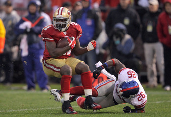 SAN FRANCISCO, CA - JANUARY 22:  Frank Gore #21 of the San Francisco 49ers runs the ball against Antrel Rolle #26 of the New York Giants during the NFC Championship Game at Candlestick Park on January 22, 2012 in San Francisco, California.  (Photo by Doug