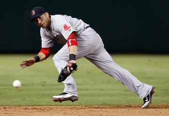 ARLINGTON, TX - AUGUST 24:  Marco Scutaro #10 of the Boston Red Sox fails to make the stop on a ground ball against the Texas Rangers at Rangers Ballpark in Arlington on August 24, 2011 in Arlington, Texas.  (Photo by Tom Pennington/Getty Images)