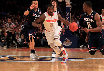 NEW YORK, NY - MARCH 11: Dion Waiters #3 of the Syracuse Orange dribbles past Shabazz Napier #13 and Kemba Walker #15 of the Connecticut Huskies during the semifinals of the 2011 Big East Men's Basketball Tournament presented by American Eagle Outfitters