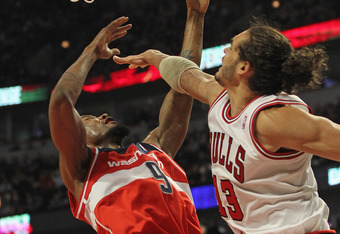 CHICAGO, IL - JANUARY 11: Joakim Noah #13 of the Chicago Bulls pressures Rashard Lewis #9 of the Washington Wizards as he shoots at the United Center on January 11, 2012 in Chicago, Illinois. NOTE TO USER: User expressly acknowledges and agrees that, by d