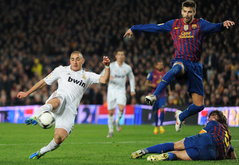 BARCELONA, SPAIN - JANUARY 25: Karim Benzema (L) of Real Madrid scores the equalizing goal past Gerard Pique (2nd R) and Carles Puyol of FC Barcelona during the Copa del Rey quarter final second leg match between Barcelona and Real Madrid at Camp Nou stad