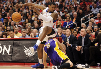 LOS ANGELES, CA - JANUARY 14:  DeAndre Jordan #6 of the Los Angeles Clippers makes a play for the ball in front of Josh McRoberts #6 of the Los Angeles Lakers during a 102-94 Clipper win at Staples Center on January 14, 2012 in Los Angeles, California.  N