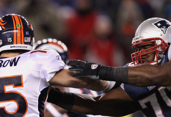 FOXBORO, MA - JANUARY 14:  Vince Wilfork #75 of the New England Patriots pressures Tim Tebow #15 of the Denver Broncos during their AFC Divisional Playoff Game at Gillette Stadium on January 14, 2012 in Foxboro, Massachusetts.  (Photo by Elsa/Getty Images