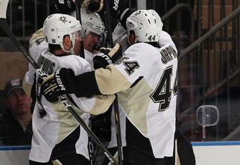 NEW YORK, NY - JANUARY 19:  Evgeni Malkin #71 of the Pittsburgh Penguins is mobbed by his team after scoring a goal against Henrik Lundqvist #30 of the New York Rangers during their game on January 19, 2012 at Madison Square Garden in New York City.  (Pho