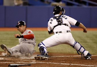 TORONTO, CANADA - SEPTEMBER 8:  Jacoby Ellsbury #2 of the Boston Red Sox slides safe past J.P. Arencibia #9 of the Toronto Blue Jays during MLB action at the Rogers Centre September 8, 2011 in Toronto, Ontario, Canada. (Photo by Abelimages/Getty Images)