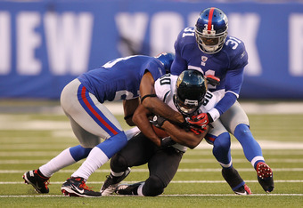 EAST RUTHERFORD, NJ - NOVEMBER 28:  Aaron Ross #31 and Corey Webster #23  of the New York Giants tackle Mike Thomas #80 of the Jacksonville Jaguars during their game on November 28, 2010 at The New Meadowlands Stadium in East Rutherford, New Jersey.  (Pho