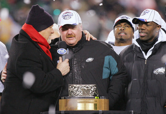PHILADELPHIA - JANUARY 23:  Head coach Andy Reid of the Philadelphia Eagles is interviewed by Terry Bradshaw before receiving the George Halas NFC Championship trophy as his players Terrell Owens #81 and Brian Dawkins #20 stand next to him after defeating