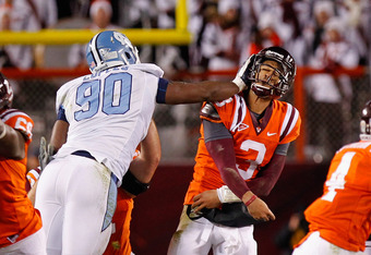 BLACKSBURG, VA - NOVEMBER 17: Logan Thomas #3 of the Virginia Tech Hokies is struck in the head after throwing the ball by Quinton Coples #90 of the North Carolina Tar Heels at Lane Stadium on November 17, 2011 in Blacksburg, Virginia. (Photo by Geoff Bur