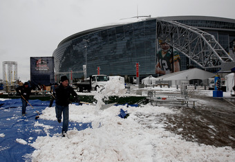 ARLINGTON, TX - FEBRUARY 04:  Workers clear snow outside the perimeter of Cowboys Stadium after a snowstorm hit the area February 4, 2011 in Dallas, Texas. More than four inches of snow fell overnight in the North Texas area. The Green Bay Packers will pl