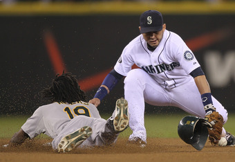 SEATTLE - SEPTEMBER 27:  Jemile Weeks #19 of the Oakland Athletics dives into second base on a double against Luis Rodriguez #1 of the Seattle Mariners at Safeco Field on September 27, 2011 in Seattle, Washington. (Photo by Otto Greule Jr/Getty Images)