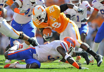 KNOXVILLE, TN - SEPTEMBER 18:  Ahmad Black #35 of the Florida Gators tackles Tauren Poole #28 of the Tennessee Volunteers in the backfield during the first half at Neyland Stadium on September 18, 2010 in Knoxville, Tennessee.  (Photo by Grant Halverson/G
