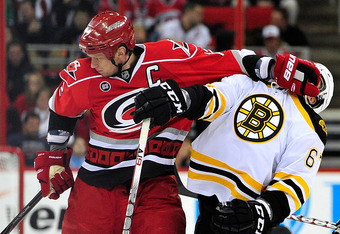 RALEIGH, NC - JANUARY 14:  Eric Staal #12 of the Carolina Hurricanes draws a penalty as he hits Benoit Pouliot #67 of the Boston Bruins in the face during play at the RBC Center on January 14, 2012 in Raleigh, North Carolina.  (Photo by Grant Halverson/Ge