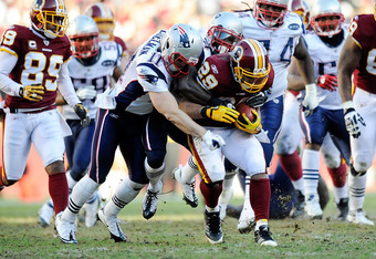 LANDOVER, MD - DECEMBER 11:   Julian Edelman #11 of the New England Patriots tackles Roy Helu #29 of the Washington Redskins during the second quarter at FedExField on December 11, 2011 in Landover, Maryland.  (Photo by Patrick McDermott/Getty Images)